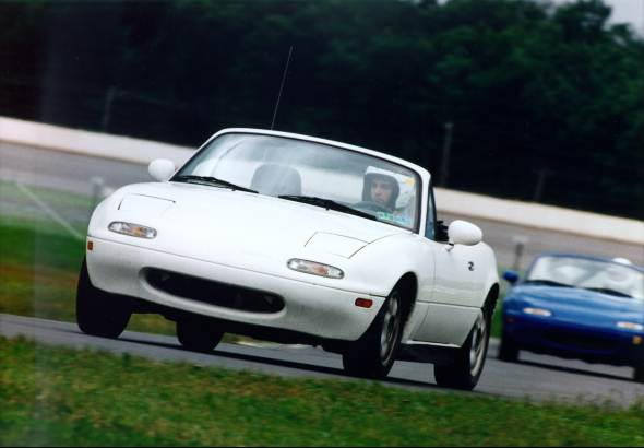 A white Miata with a blue Miata